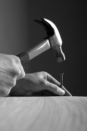 carpenter hammering a nail into a board