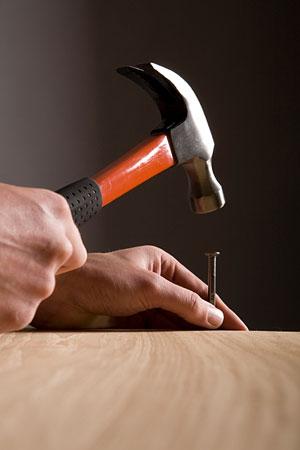 hammer and nail - carpenter hammering a nail into a board
